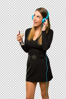 Woman with champagne celebrating new year 2019 listening to music with headphones