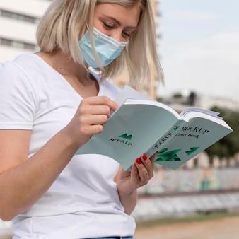 路上で本を読んでマスクを持つ女性