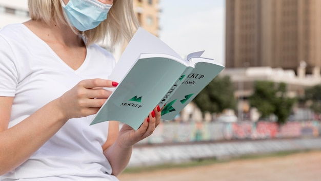 Woman with mask reading book on street