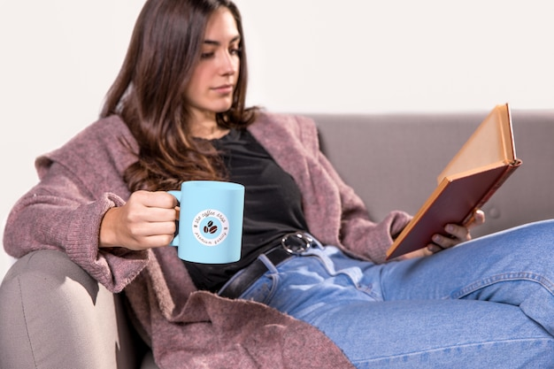 ソファで読書マグカップを持つ女性