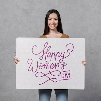 プラカードを保持している広い笑顔を持つ女性