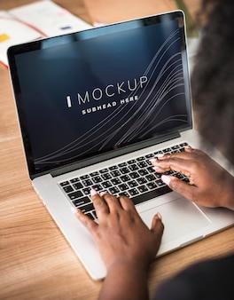 ノートパソコンの画面のモックアップに取り組んでいる女性