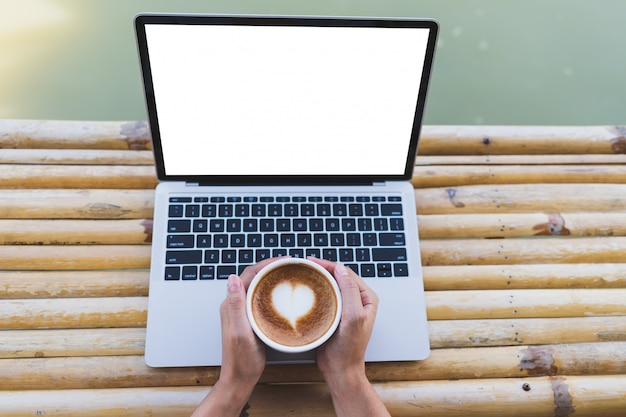Women hand holding a hot espresso mug put on a laptop mockup on a bamboo table, outdoor