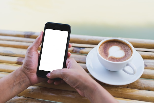 Women hand holding a smartphone mockup on a bamboo table, hot espresso, outdoor