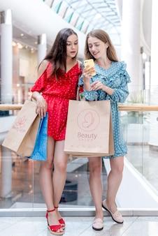 モールで買い物袋を保持している女性
