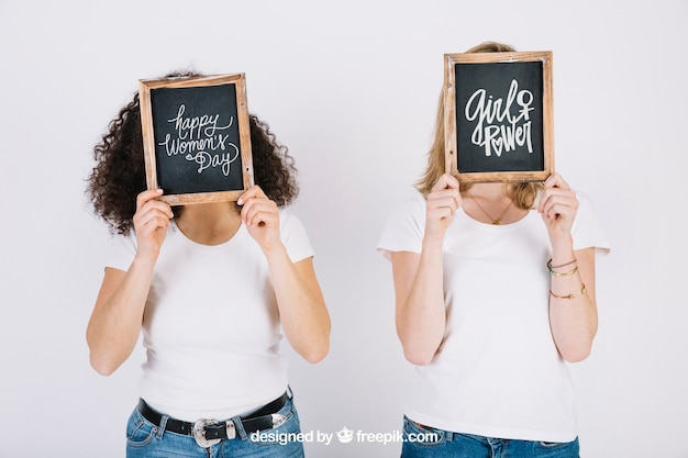 Women holding slate in front of face