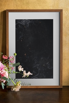 Wooden frame mockup by the flowers