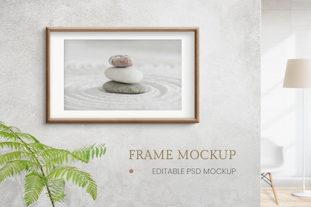 Wooden picture frame mockup psd with zen stones photo on the wall interior concept