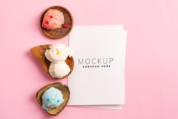 パステルピンクのモックアップに紙のシートで新鮮な自然なカラフルなアイスクリームの木製プレート