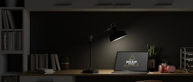 열린 노트북과 테이블 램프의 조명이 있는 야간 작업 공간 늦은 밤 어두운 작업 공간