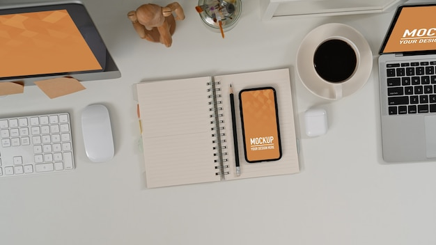 흰색 테이블에 검은 화면 스마트 폰 및 사무 용품 작업 영역