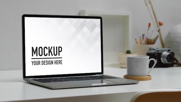 Рабочее пространство с макетом цифрового ноутбука, чашкой кофе и принадлежностями