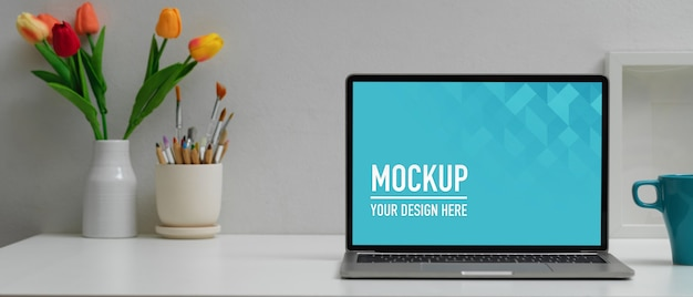 Workspace with digital laptop mockup, coffee cup and supplies