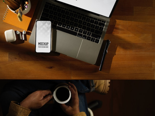 Workspace with digital phone mockup with mug