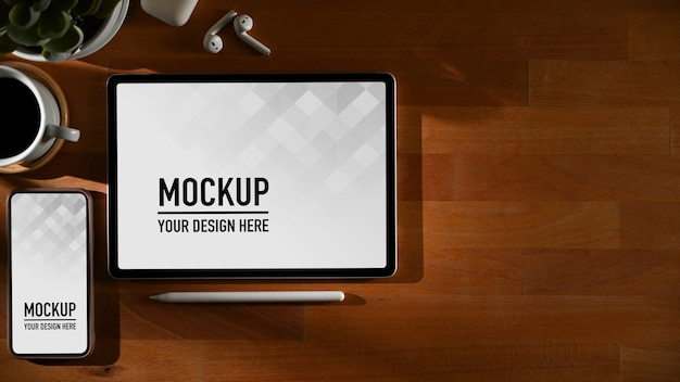 Workspace with digital phone and tablet mockup with mug