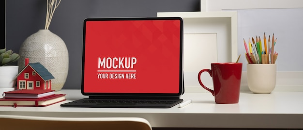 Workspace with digital tablet mockup and supplies