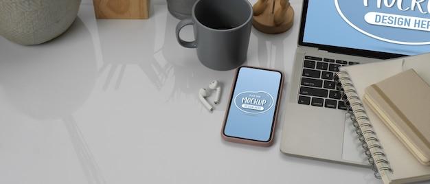 スマートフォンのモックアップを備えたワークスペース、ノートブックの横にあるラップトップ