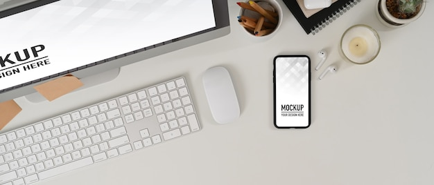 Workspace with mockup smartphone and desktop computer with office supplies