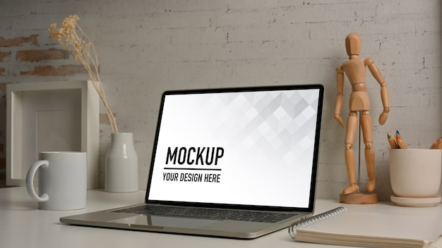 Worktable with laptop mockup and decorations in home office room