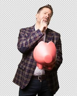 Worried mature man holding a piggy bank