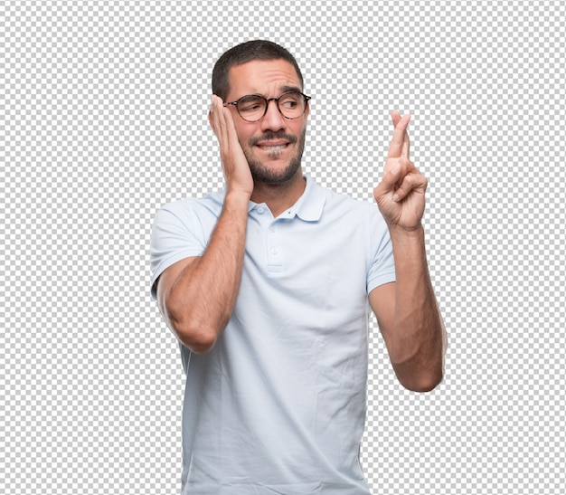 Worried young man doing a gesture of crossed fingers