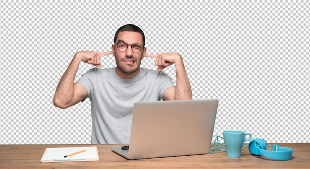 Worried young man sitting at his desk and covering his ears with his hands