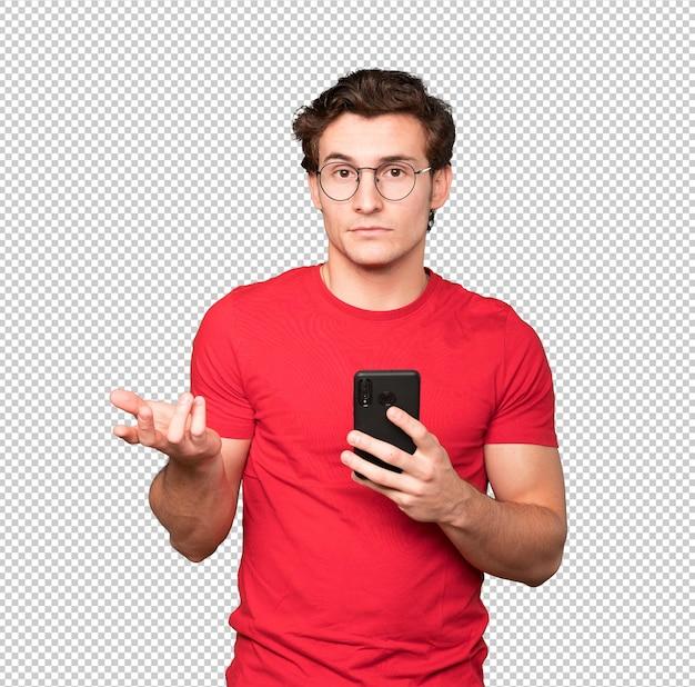 Обеспокоенный молодой человек, использующий свой мобильный телефон
