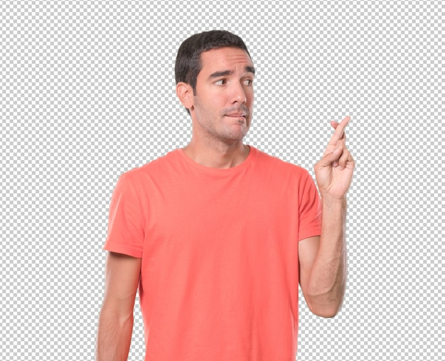 Worried young man with crossed fingers gesture