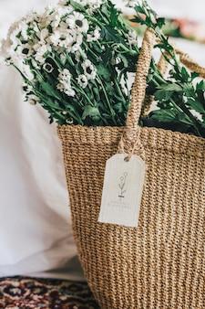 白いアネモネの花でいっぱいの編まれたバスケット