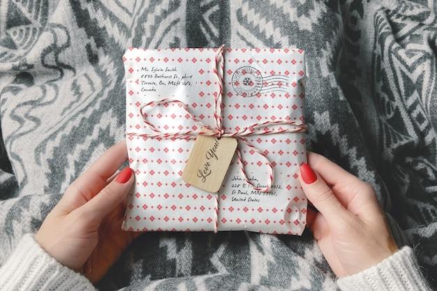Обернутая посылка в макете рук женщины