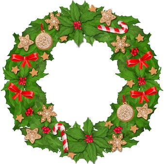 Wreath of holly leaves and berries decorated with toys and gingerbread.