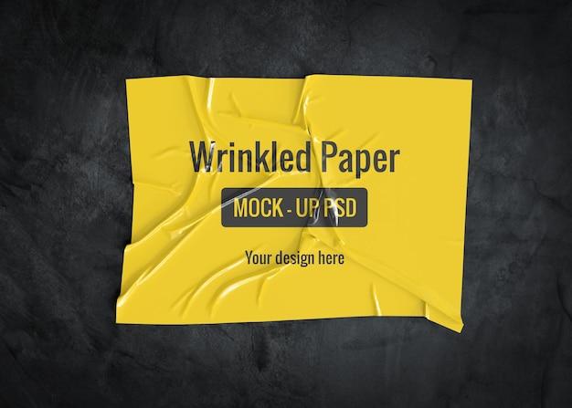 暗い表面のしわのある紙のモックアップ