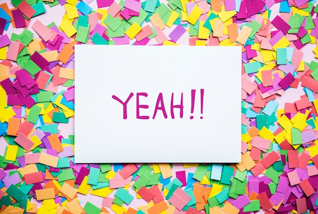 Yeah! text on paper and colorful party confetti background party concept