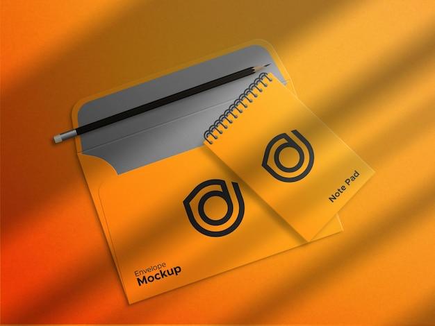 작은 메모장 모형 아래 노란색 봉투