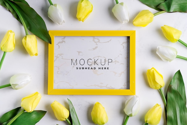 Yellowtulips with blank picture frame on white marble background, copy space