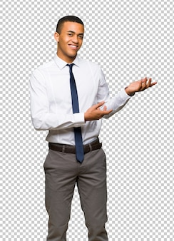 Young afro american businessman extending hands to the side for inviting to come