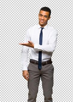 Молодой афро американский бизнесмен представляя идею пока смотрящ усмехающся к