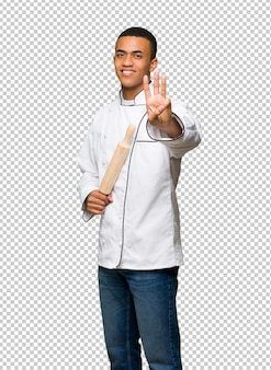 Young afro american chef man happy and counting three with fingers
