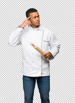 Young afro american chef man having doubts while scratching head