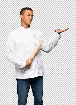 Young afro american chef man holding copyspace imaginary on the palm to insert an ad