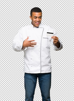 Young afro american chef man holding a credit card and surprised