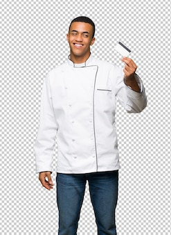 Young afro american chef man holding a credit card and thinking