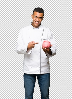 Young afro american chef man holding a piggybank