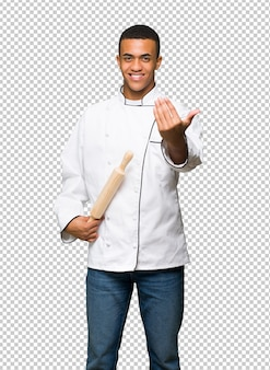 Young afro american chef man inviting to come with hand. happy that you came