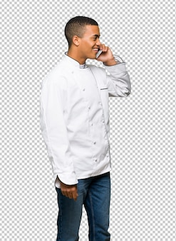 Young afro american chef man keeping a conversation with the mobile phone
