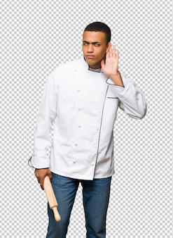Young afro american chef man listening to something by putting hand on the ear