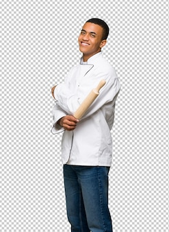 Young afro american chef man looking over the shoulder with a smile