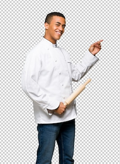 Young afro american chef man pointing finger to the side in lateral position