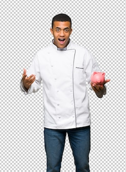 Young afro american chef man surprised while holding a piggybank