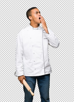 Young afro american chef man yawning and covering wide open mouth with hand